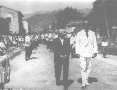 """Esta foto de principios de los sesenta, muestra a Don Benito Alba, alcalde de La Adrada, con D. León Mª González Ayuso (de blanco) de la Banda de Guadamur y el resto de la Banda durante una procesión de las fiestas de El Salvador. La foto está tomada justo donde está el bar El Peral. D. León Mª González Ayuso, fue director de dicha banda desde 1939 a 1983 y compuso el pasodoble """"La Adrada"""" . Esta banda amenizó las fiesta de La Adrada, en las décadas de los sesenta y setenta. En 2009 la Banda de Música de Guadamur celebró su 175 aniversario."""