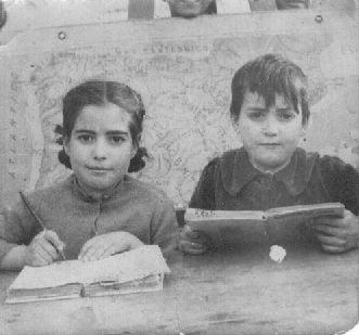 Los hermanos Ángel y Lucía Diaz. Posando en la tradicional foto escolar de aquella época, con mapa incluido. Hacia 1950